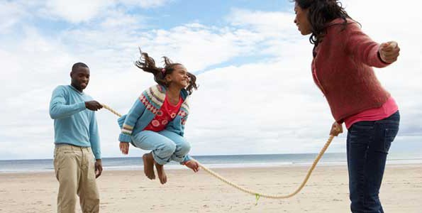 Young girl skipping rope on the beach