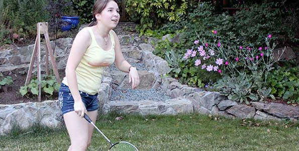 Marcelita Grove playing badminton in the back yard