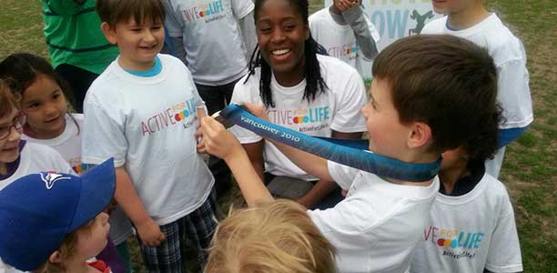 Shelley-Ann Brown shows her Olympic silver medal to children at an Active for Life event