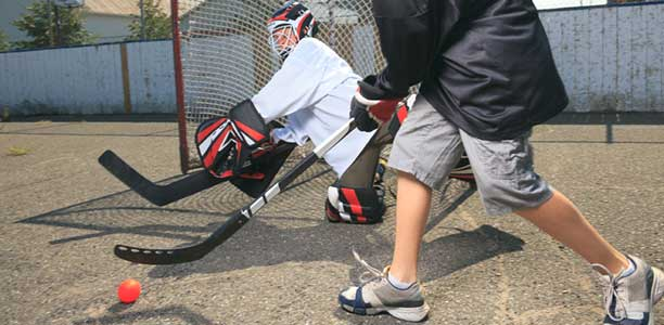 Two boys playing street hockey