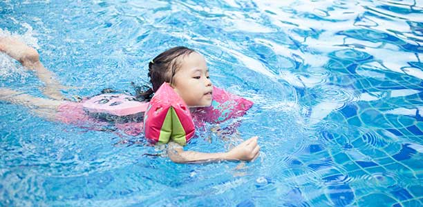 A young girl swims with water wings