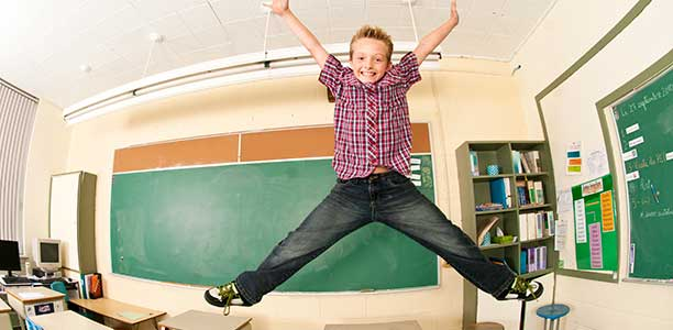 A boy jumps for joy in the classroom