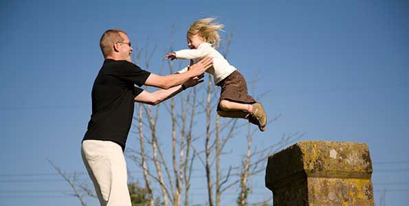 A dad helps his child jump from a pillar