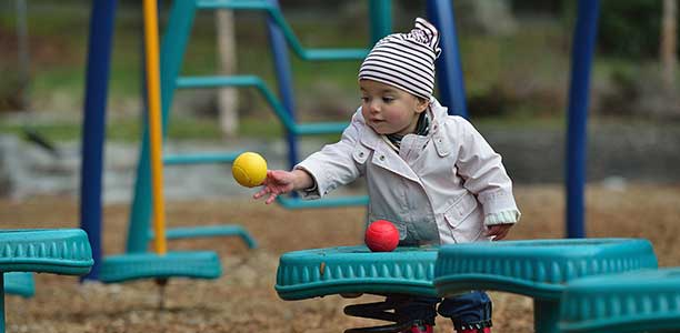Young toddler throwing a ball in a playground