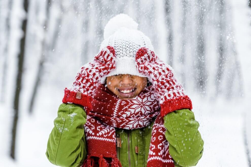 Child dressed for winter, wearing coat, hat, mitts, and scarf.