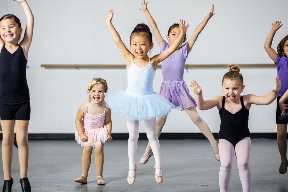 A diverse young group of students practice in musical theatre and ballet combo dance class