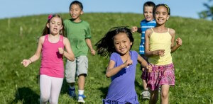 A multi-ethnic group of elementary age children, playing tag together at the park, running outside on a beautiful sunny day - smiling and looking at the camera.
