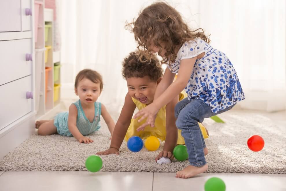 Three excited little girls playing together at the playroom, trying to catch balls. Balls jump everywhere.