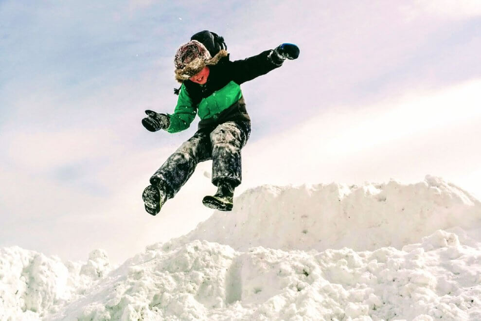Boy jumping off snow bank