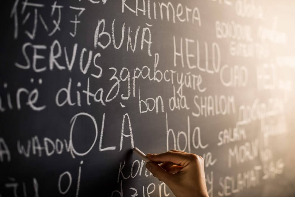 person writes on chalkboard in various languages
