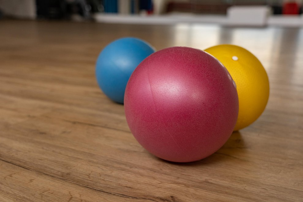 three primary coloured rubber balls on gym floor