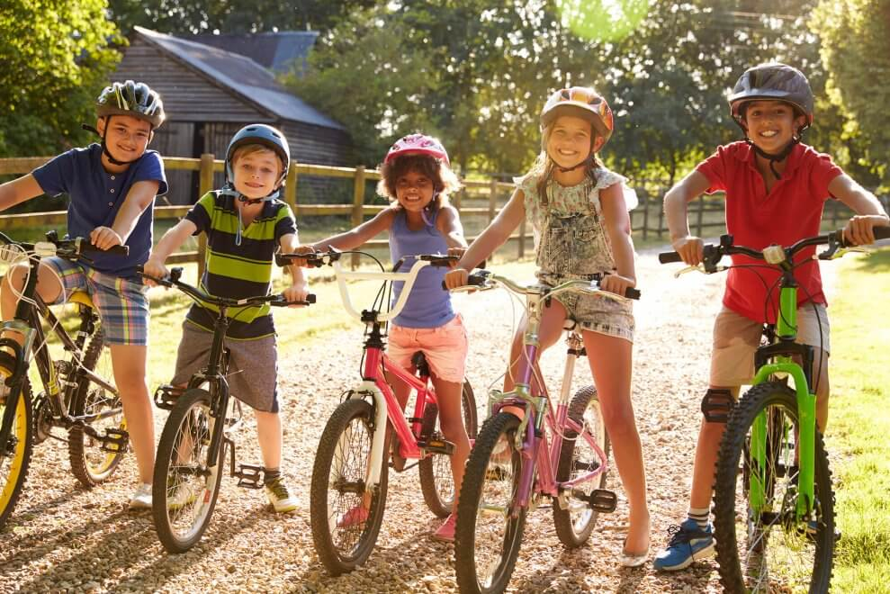 children standing astride bicycles